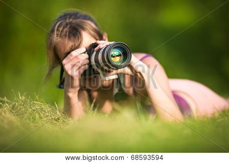 Pretty female photographer lying in grass, on a lovely summer day, taking pictures with her DSLR camera and a telephoto lens