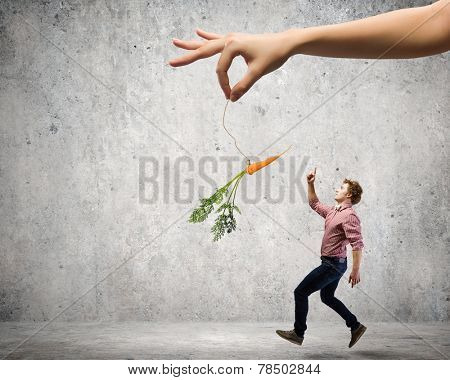 Young man in casual teased by carrot hanging on rope poster