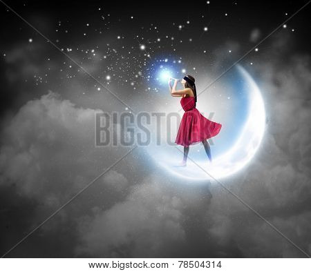 Young woman in red dress standing on moon and playing fife poster