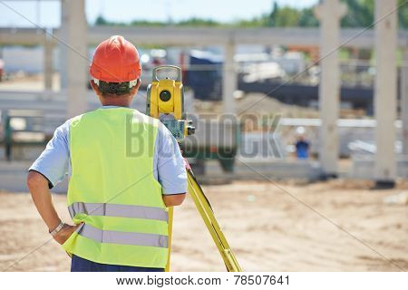 Portrait of builder worker with theodolite transit equipment at construction site outdoors during surveyor work