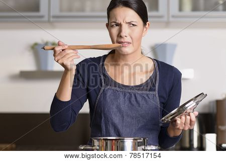 Young Cook Tasting Her Food With A Grimace