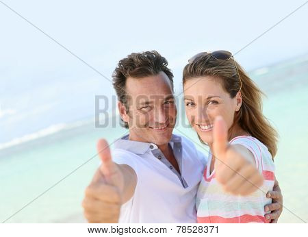 Happy couple showing thumbs up to camera