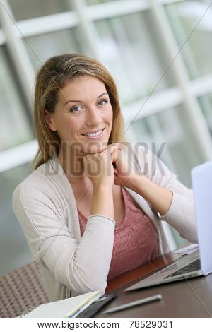 Portrait of middle-aged woman teleworking