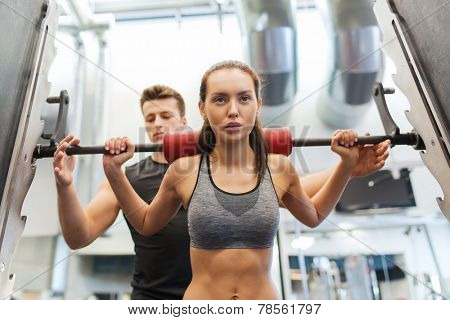 sport, fitness, teamwork, weightlifting and people concept - young woman and personal trainer with barbell flexing muscles in gym poster