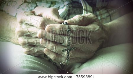 Senior Woman Hands Holding Rosary While Praying
