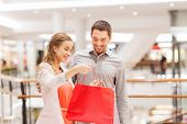 sale, consumerism and people concept - happy young couple showing content of shopping bags in mall poster