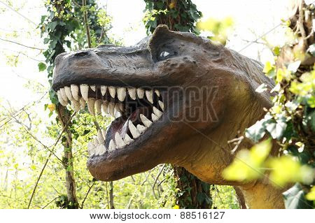 Large Head Of An Allosaurus Dinosaur At The Forest