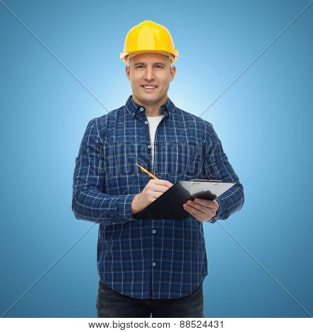 repair, construction, building, people and maintenance concept - smiling male builder or manual worker in helmet with clipboard taking notes over blue background