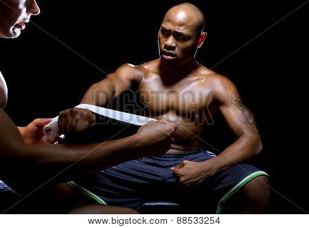 Boxer with Trainer Applying Athletic Tape