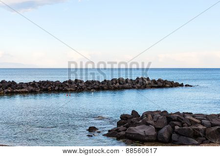 Stones Breakwater Near Beach Of Giardini Naxos