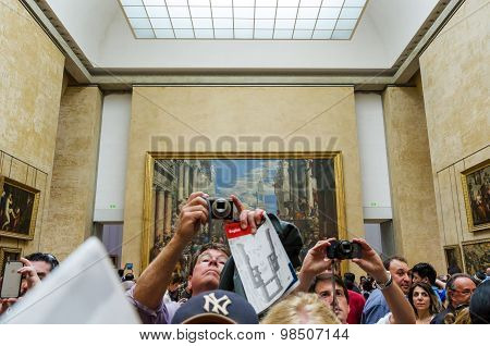 Paris, France - May 13, 2015: Visitors Take Photos Of Leonardo Davinci's mona Lisa At Louvre Museum