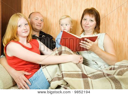 Family Reading On Couch