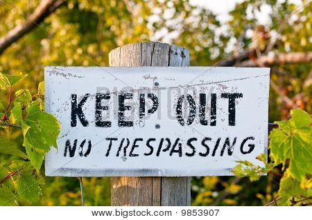 Weathered Keep Out Sign On A Wooden Post