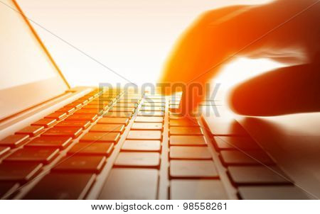 Close up of a hand typing on laptop keyboard.