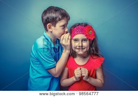 Teen boy whispering in the ear of teen girl on a gray background