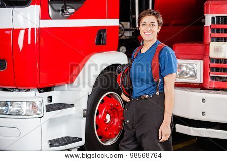 Portrait of happy firewoman holding helmet while standing against firetruck at station