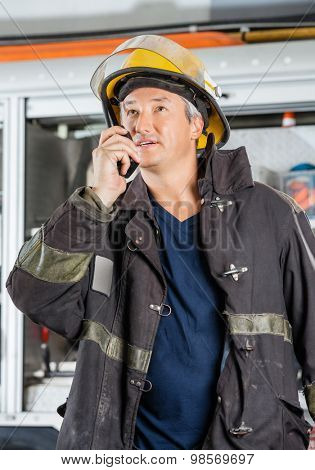 Mature fireman looking away while using walkie talkie at fire station