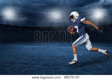 American Football Player Running for a touchdown in a large outdoor professional football stadium at night