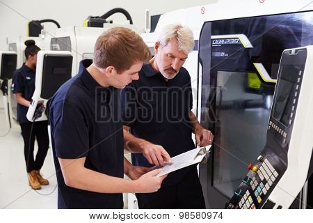 Male Apprentice Working With Engineer On CNC Machinery