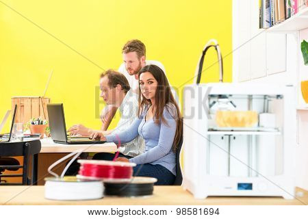 Portrait of female designer sitting with colleagues discussing in 3D printing studio