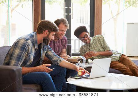Three Businessmen Having Working Lunch In Office