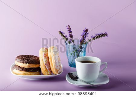 Delicious Colorful Donuts On Dish,with Cup And Flowers