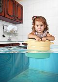 Funny little child swims in pan in the flooded kitchen mess creative concept poster