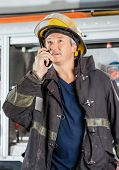 Mature fireman looking away while using walkie talkie at fire station poster
