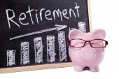 Pink piggy bank with glasses standing next to a blackboard with retirement savings message. Sharp focus on the piggy bank. poster