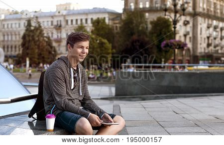 happy young man with a tablet on the street of a big city