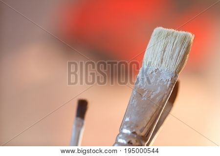 Artistic brushes in the workshop. Brushes artist on an abstract blurred background in the studio for artists.