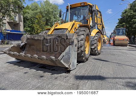 Heavy construction bulldozer and vibrating roller during the construction of a road on a city street at noon