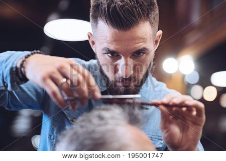 Cutting hair. Nice serious bearded barded holding a comb and cutting his clients hair while working