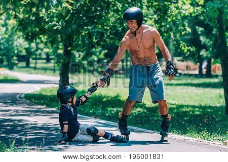 Grandfather Giving Hand To His Grandson After Minor Roller Skating Incident, Color Image, Toned Imag