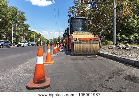 Orange road cones protect the working area for heavy vibrating compactors on a city street