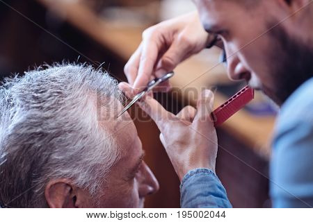 Being careful. Pleasant serious good looking barber holding scissor and cutting hair while working in the barbershop