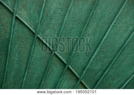 Texture of an old green iron wall with long bars