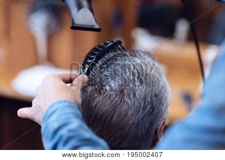 At the barbershop. Professional experienced nice barber holding a hair dryer and using a brush while styling his clients hair