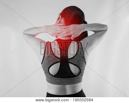 Young Asian woman in workout cloth having Neck pain with red focus dot on isolated background. back view people.