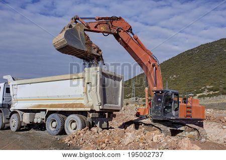 Bulldozer and Truck, Bulldozer loading sand into the truck