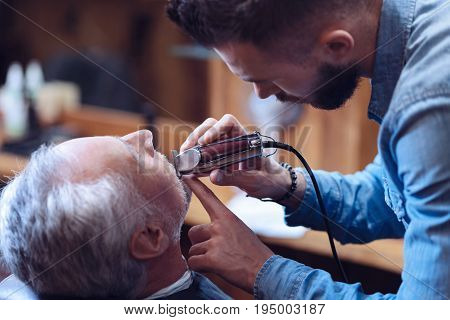 Perfect beard styling. Pleasant hard working experienced barber holding an electric shaver and styling his clients beard while leaning over him