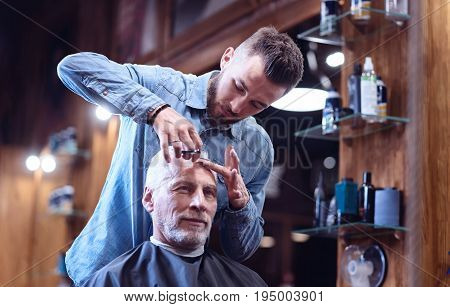 Fashion tendencies. Positive delighted elderly man sitting in the armchair and wearing a cape while having his hair cut