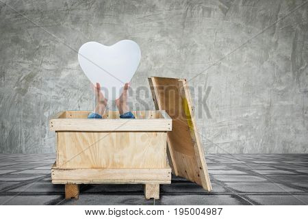 Heart-shaped balloon in the hands of a woman in old wooden box on concrete floor and concrete wall for background.