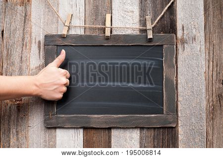 Female Hand Showing Thumbs Up On Chalk Board.