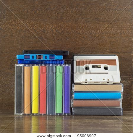 Stack of old colorful audio cassettes and cases on the brown wooden shelf