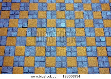 Texture of colored square paving tiles on the road