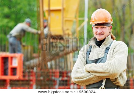 one cheerful builder worker in work wear and hardhat at construction site