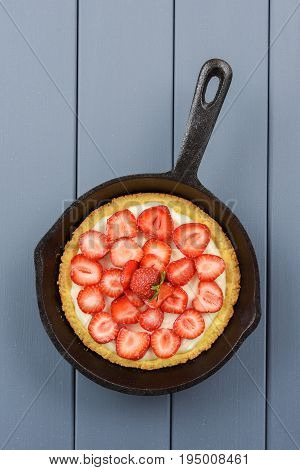 Homemade strawberry pie with fresh strawberries in cast iron skillet vertical