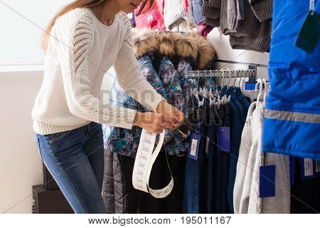 Young woman-seller glues prices the goods - kids clothes