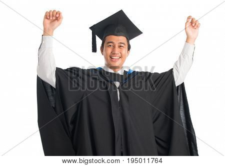 Attractive Southeast Asian male university student in graduation gown arms raised celebrating success, standing isolated on white background.